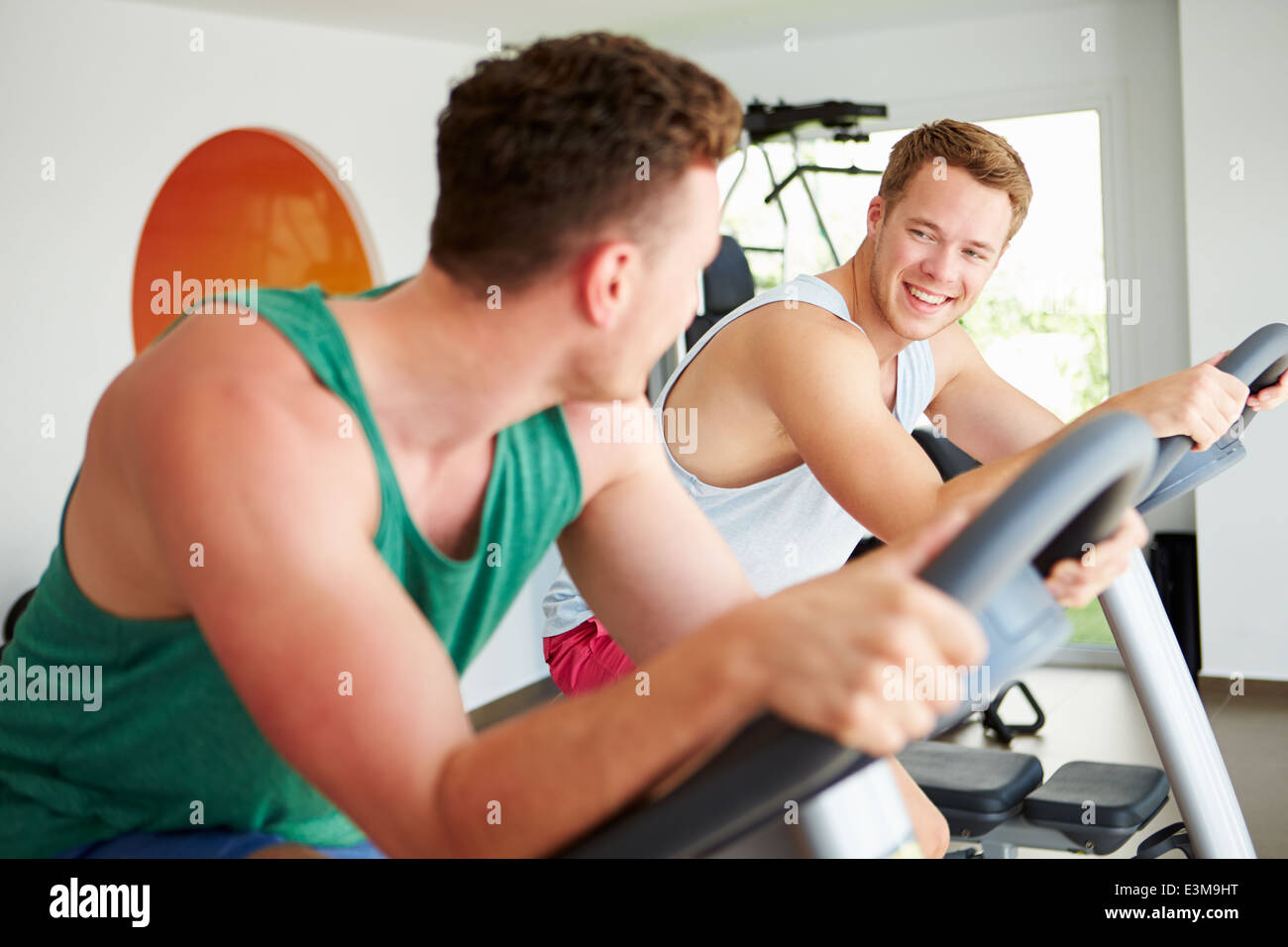 Two Young Men Training In Gym On Cycling Machines Together Stock Photo