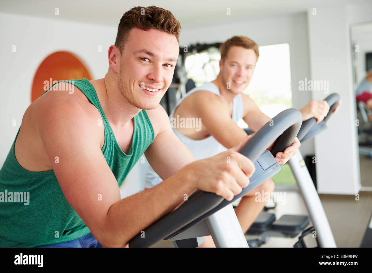 Two Young Men Training In Gym On Cycling Machines Together - Stock Image