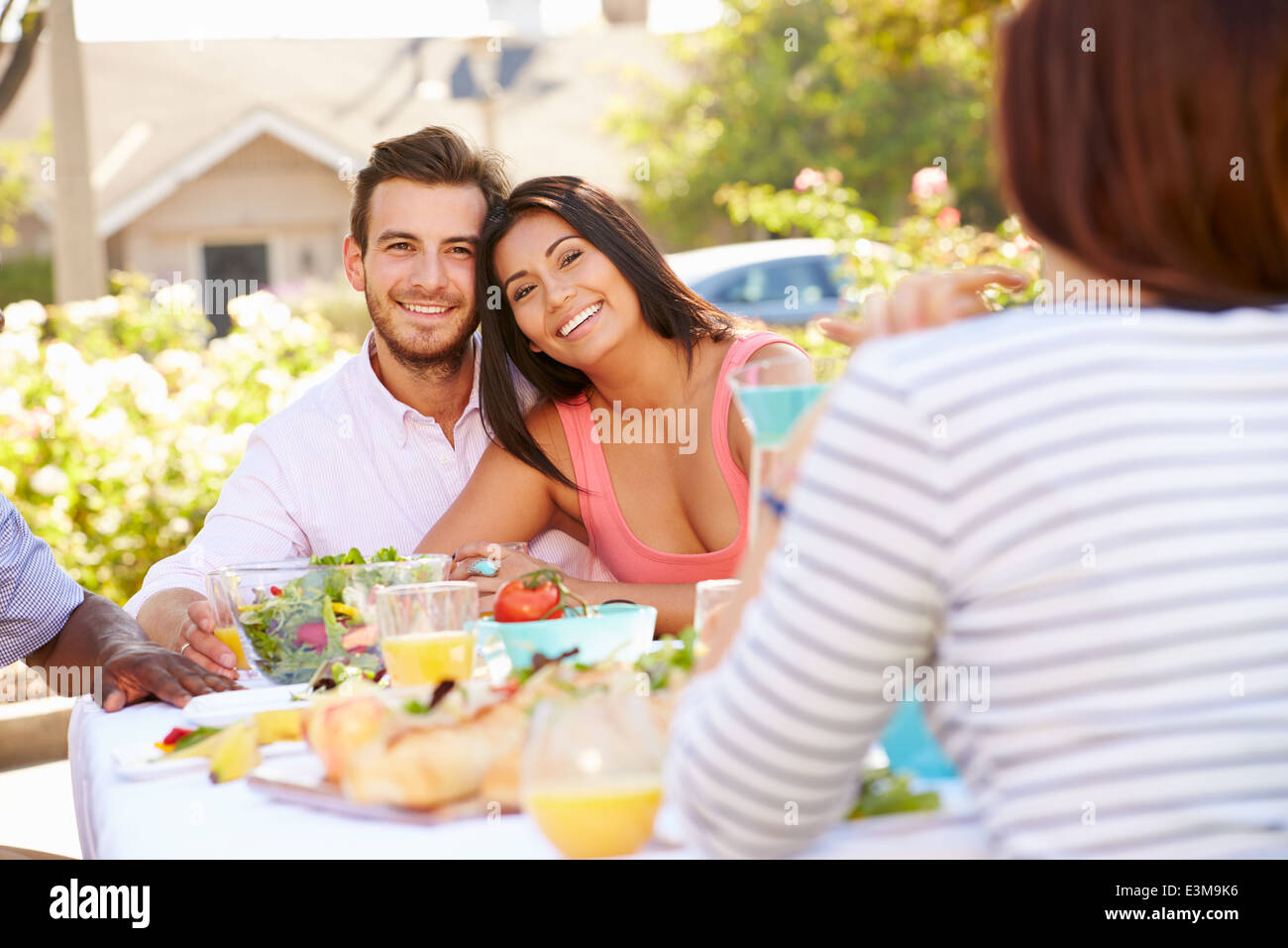 Group Of Friends Enjoying Meal At Outdoor Party In Back Yard - Stock Image