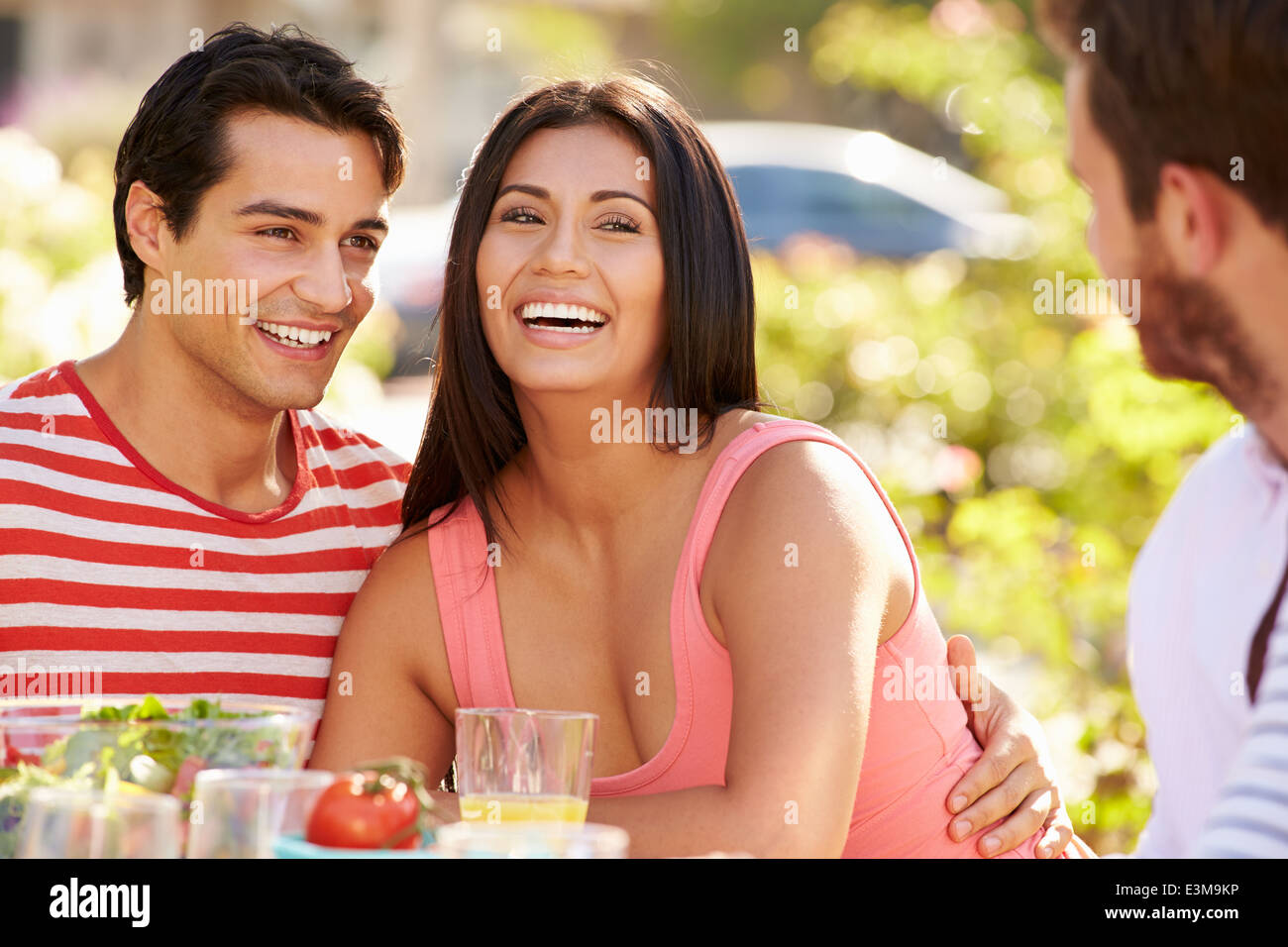 Group Of Friends Enjoying Meal At Outdoor Party In Back Yard Stock Photo