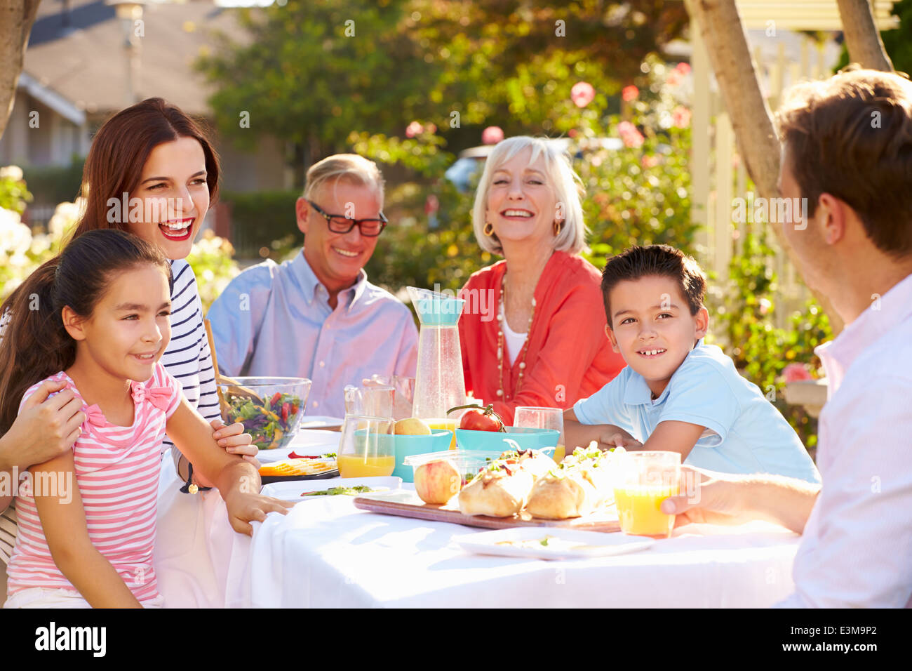 Multi-Generation Family Enjoying Outdoor Meal In Garden - Stock Image