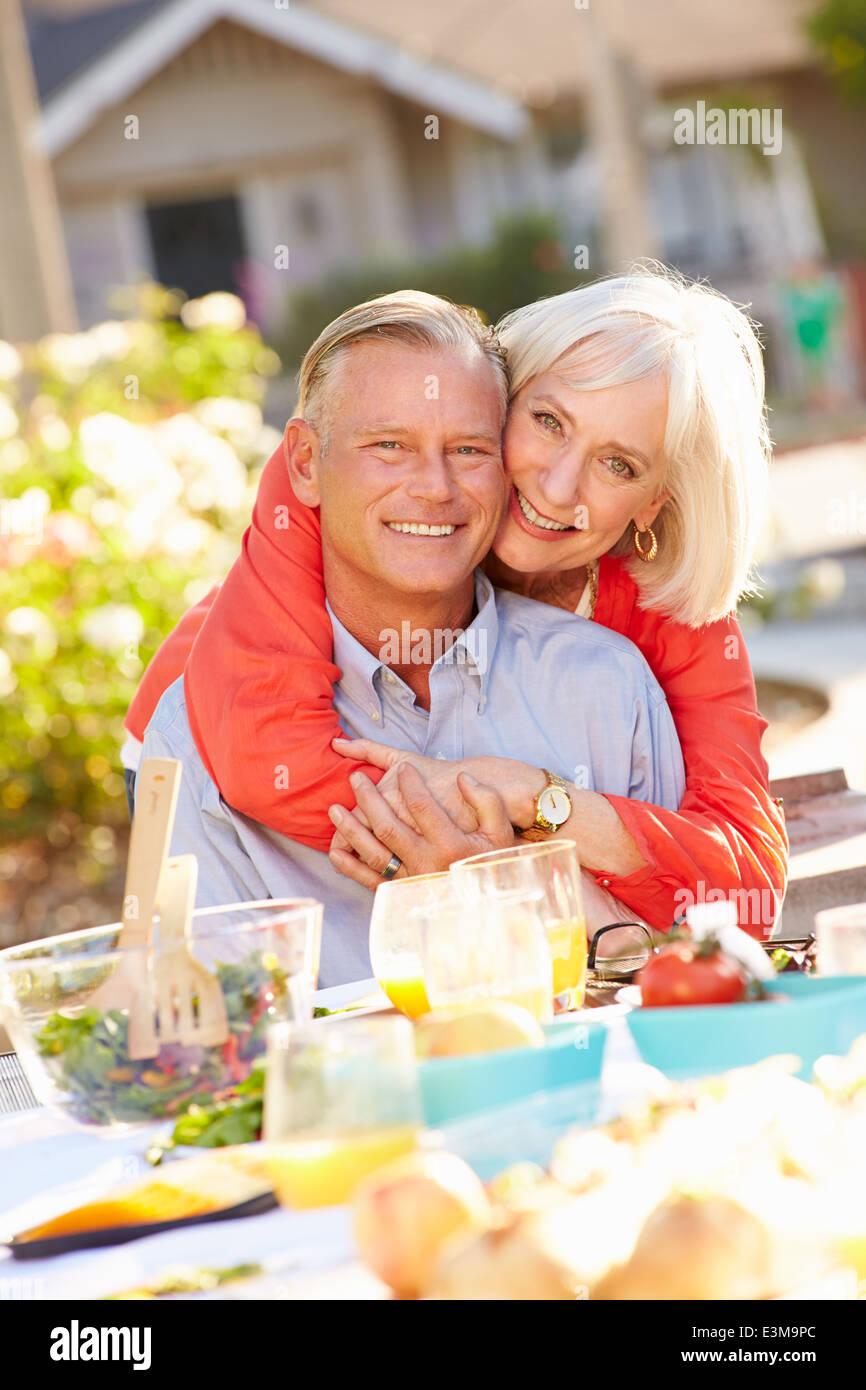 mature romantic couple enjoying outdoor meal in garden stock photo