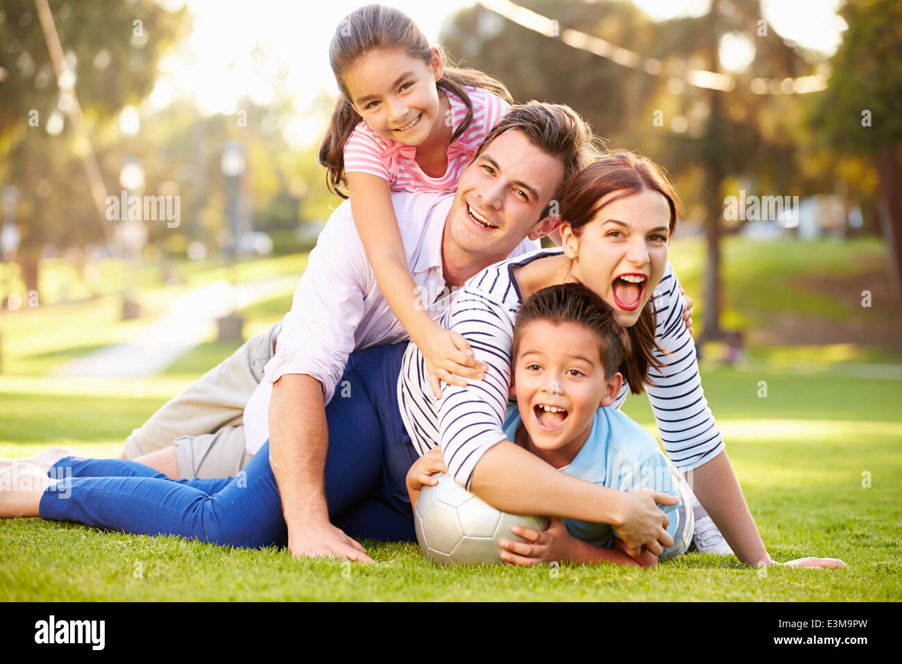 Family Lying On Grass In Park Together - Stock Image