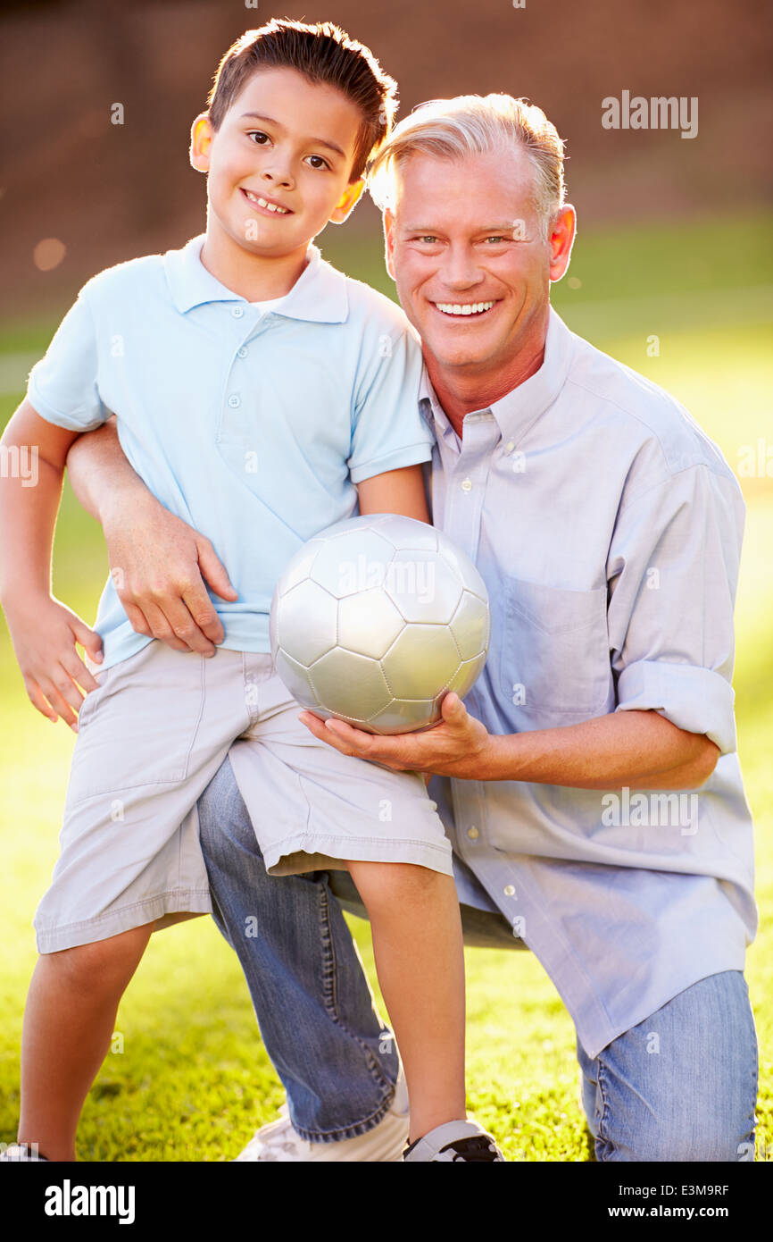 Grandfather Playing Football With Grandson In Park Stock Photo