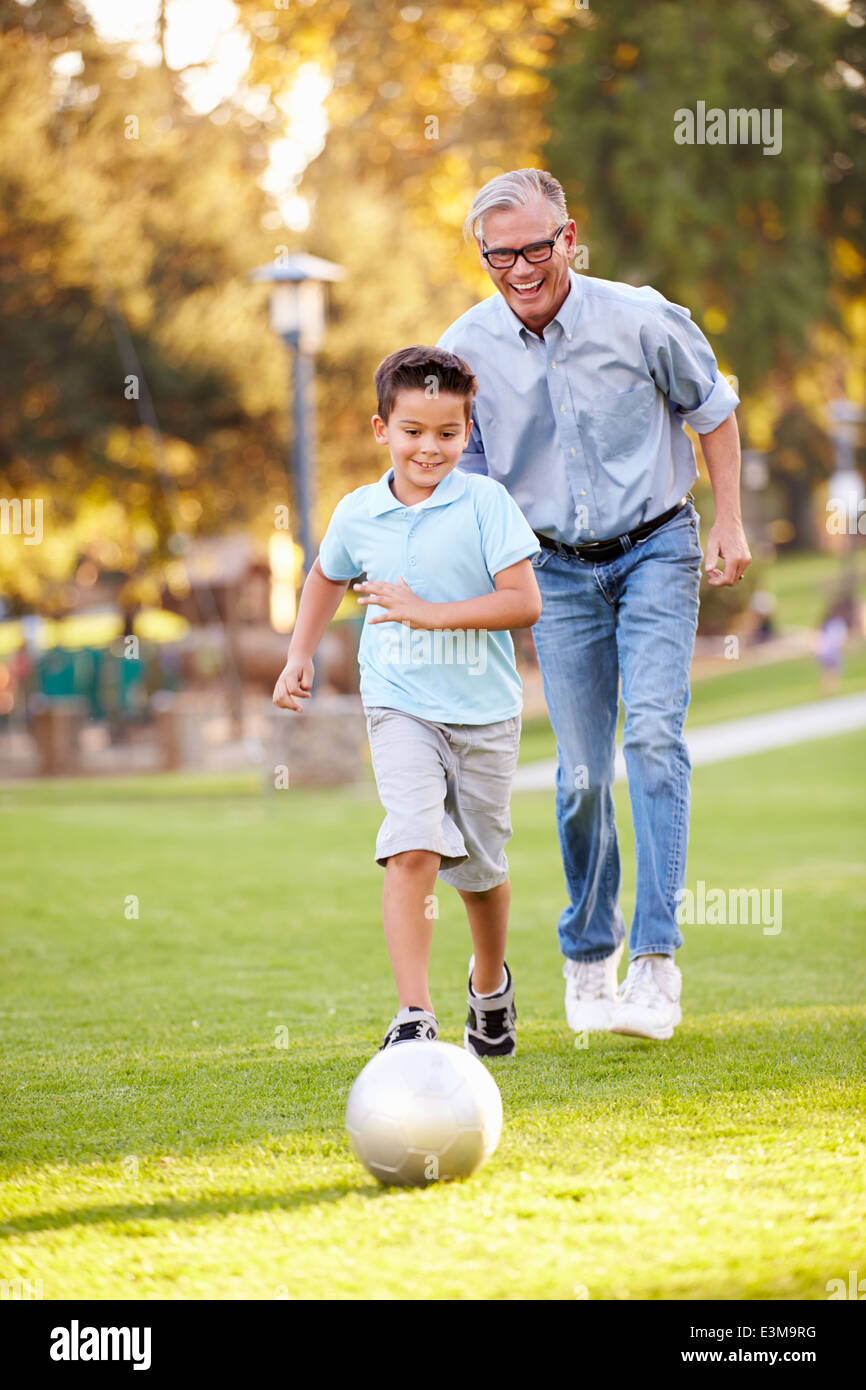 Grandfather Playing Football With Grandson In Park - Stock Image