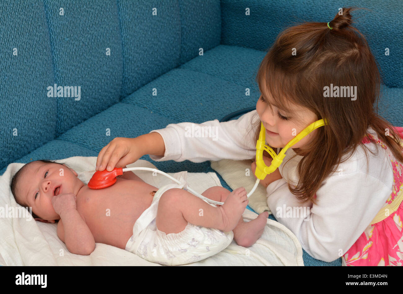 Happy little girl ,play pretend to be a midwife or a doctor, checking the heart rat of her newborn baby sister. - Stock Image