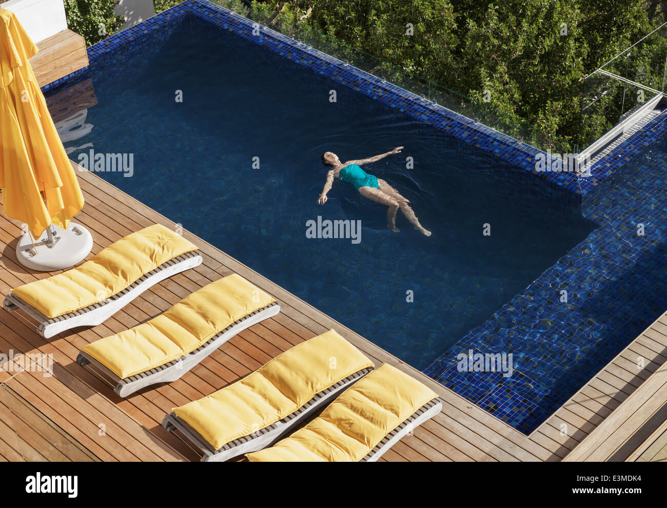 Woman floating in luxury swimming pool - Stock Image