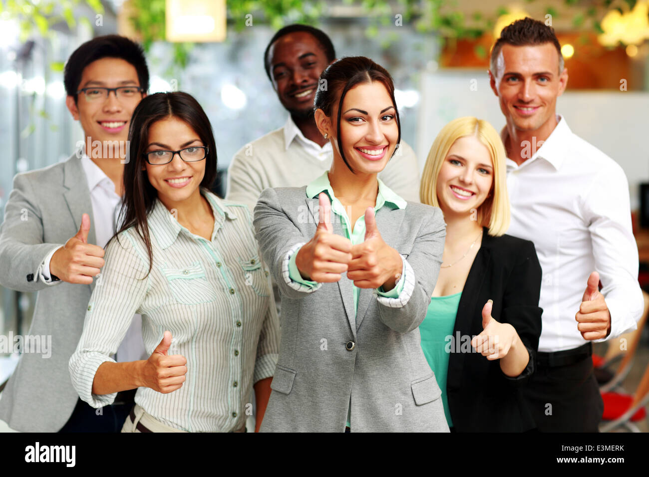 Happy business group giving thumbs up - Stock Image
