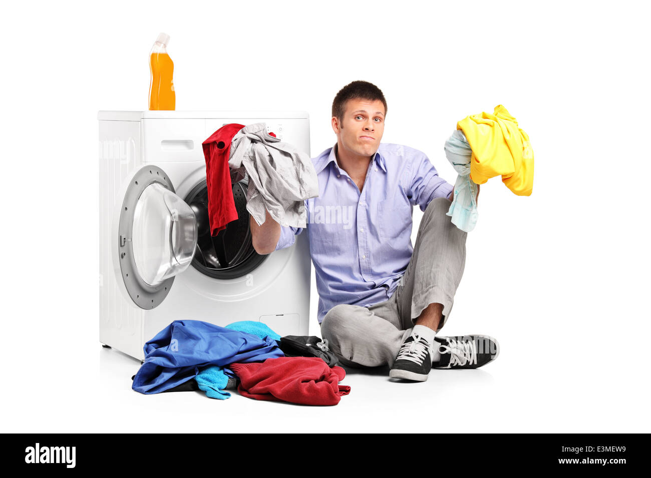 Confused young man doing laundry seated by a washing machine - Stock Image