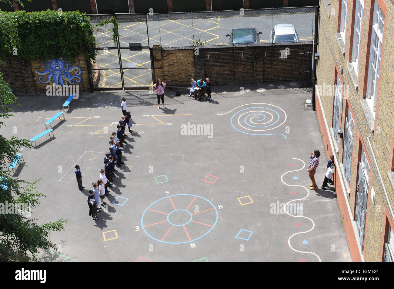School children playing in a school playground in an inner city london primary school. - Stock Image