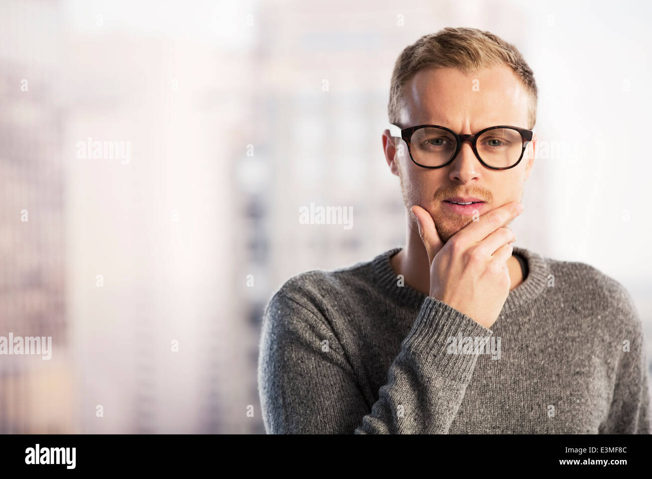 Pensive businessman with hand on chin - Stock Image