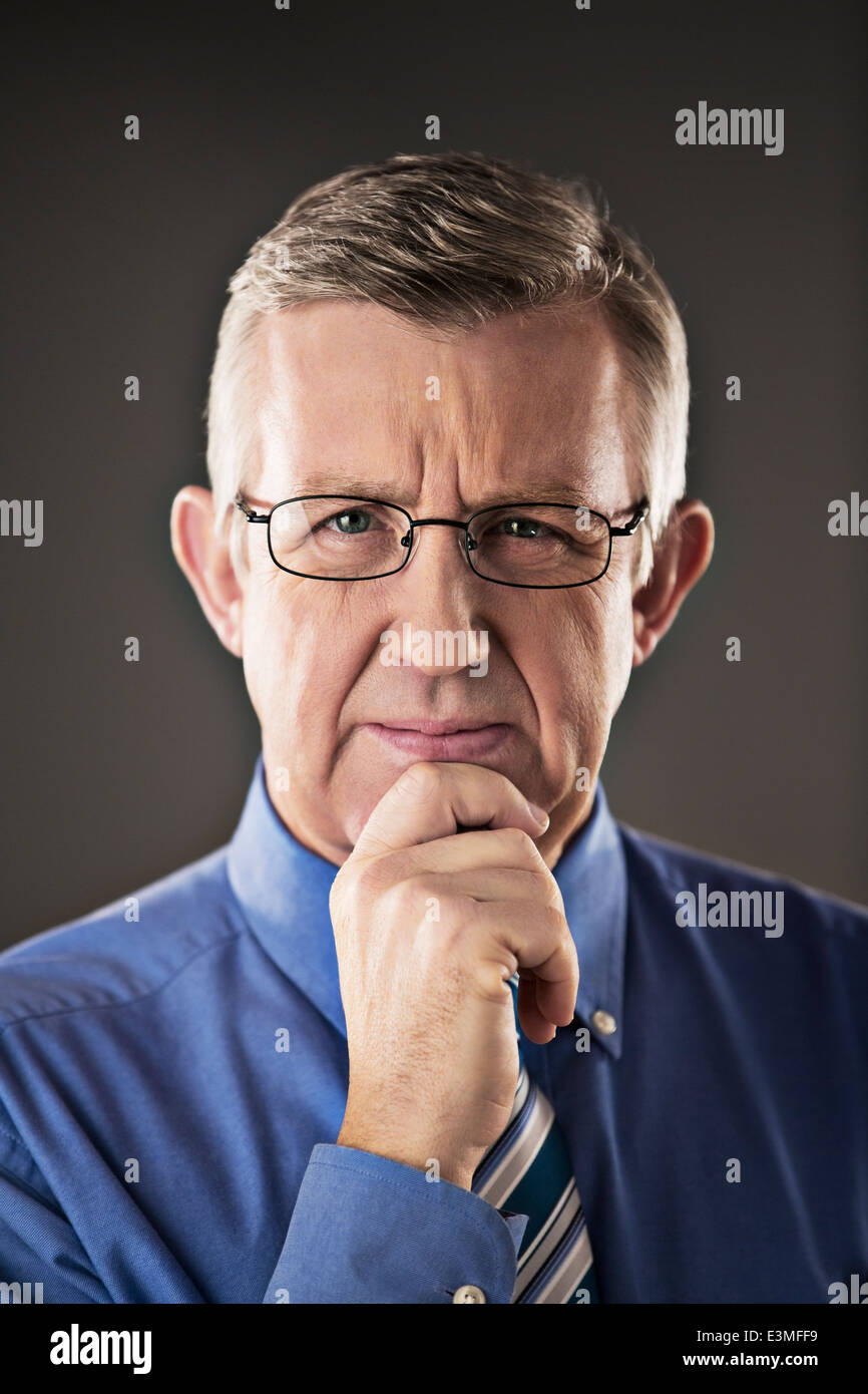 Portrait of confident businessman with hand on chin - Stock Image