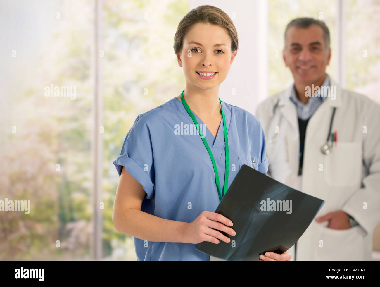 Portrait of smiling nurse with x-ray - Stock Image
