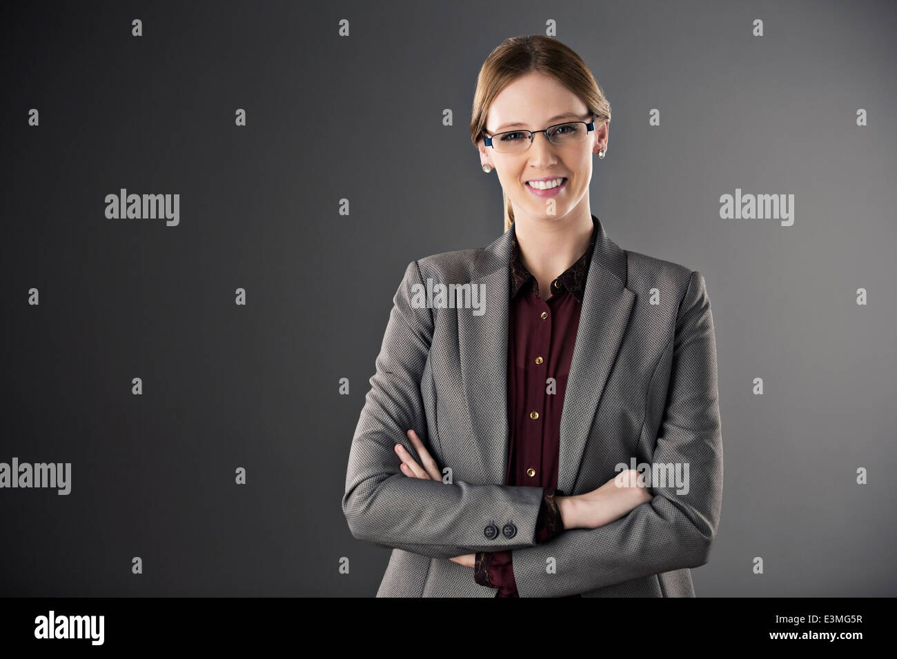 Portrait of confident businesswoman with arms crossed - Stock Image
