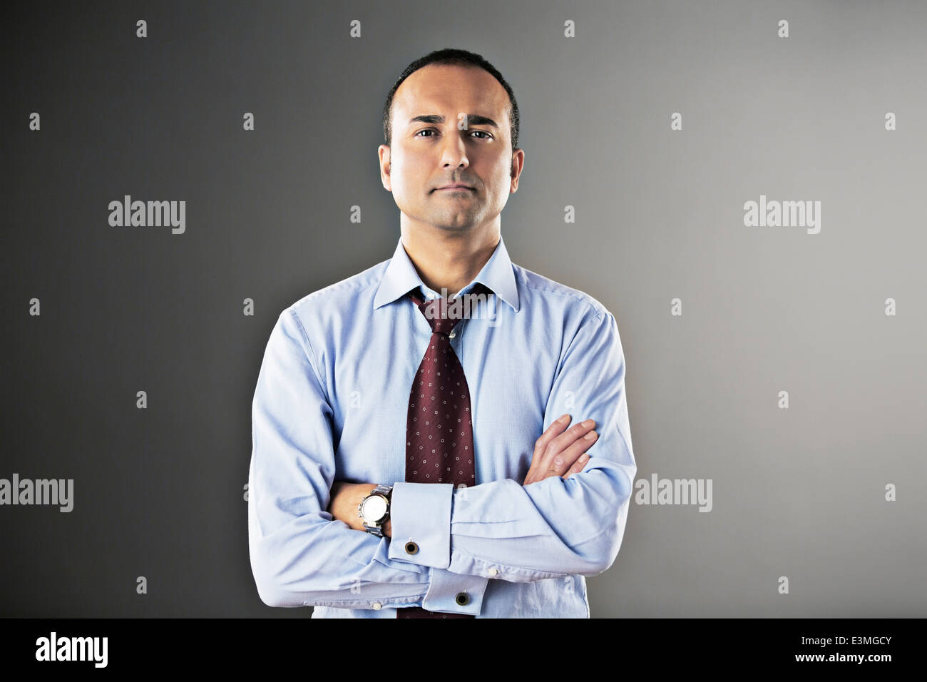 Portrait of confident businessman with arms crossed - Stock Image