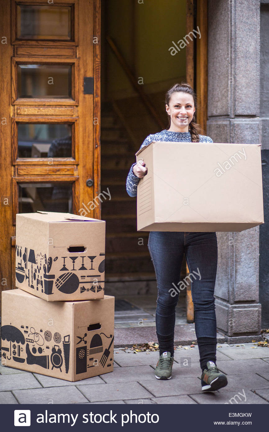 Full length portrait of young woman with cardboard box walking on sidewalk - Stock Image