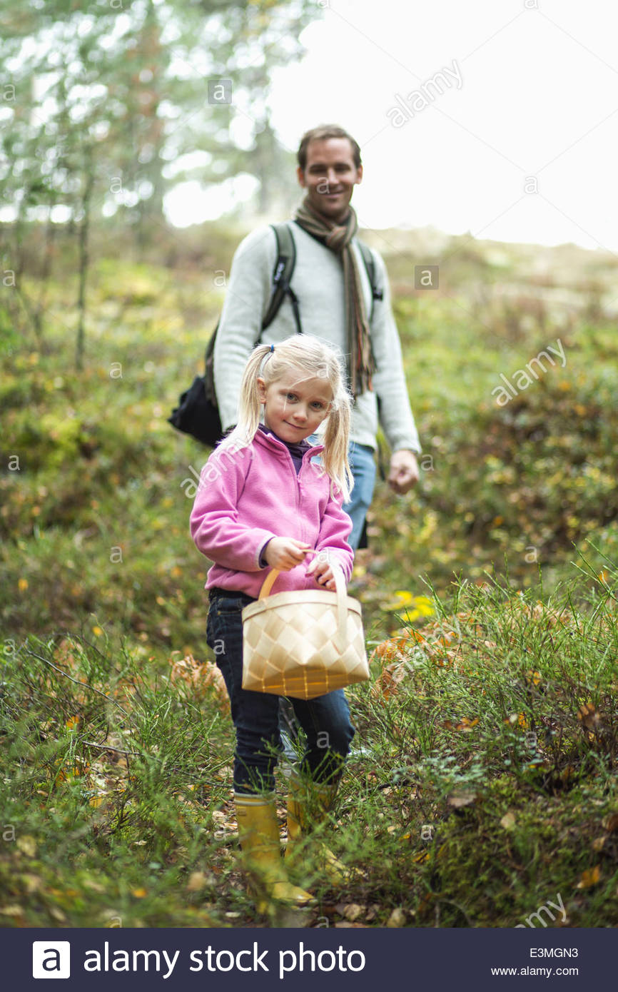 Full length portrait of girl carrying basket with father in background at field - Stock Image