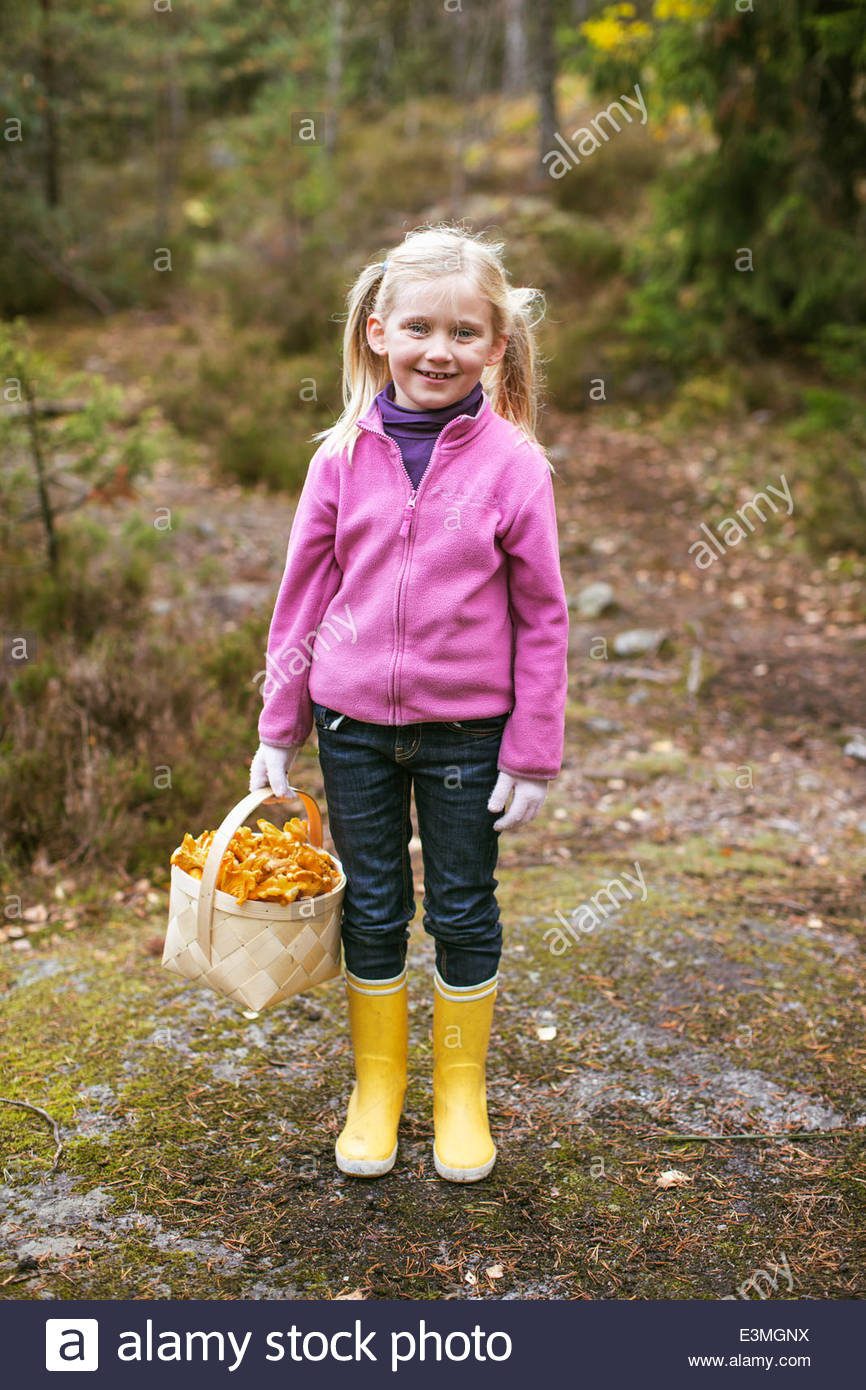Full length portrait of happy girl carrying basket of mushrooms in forest - Stock Image