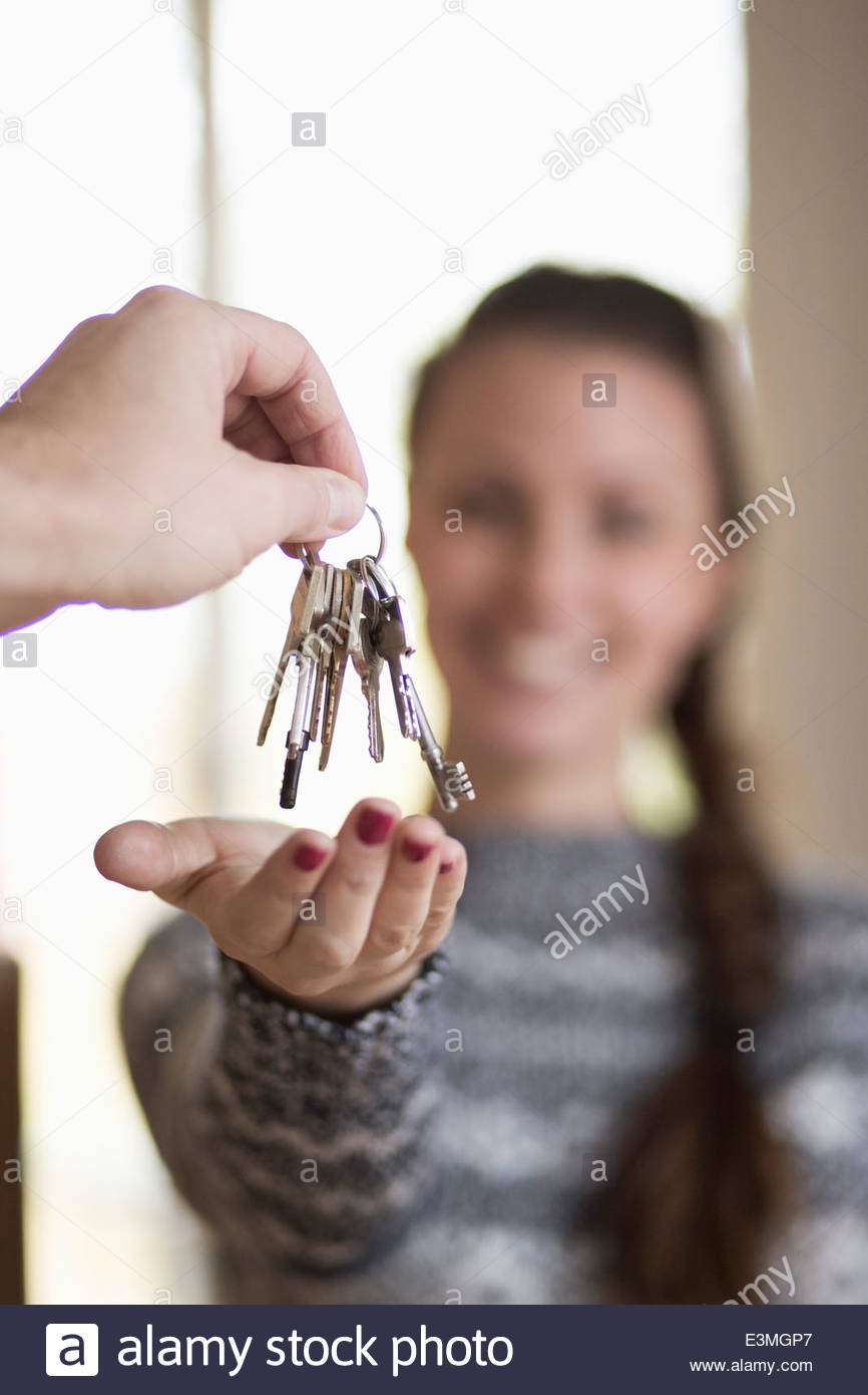 Young woman receiving new home key - Stock Image