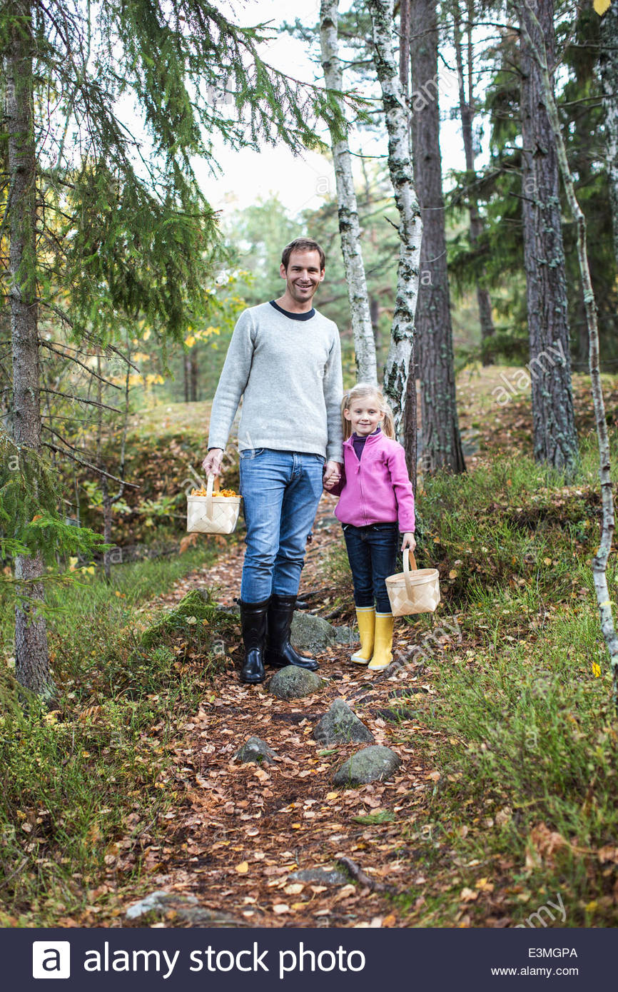 Full length portrait of father and daughter carrying baskets in forest - Stock Image