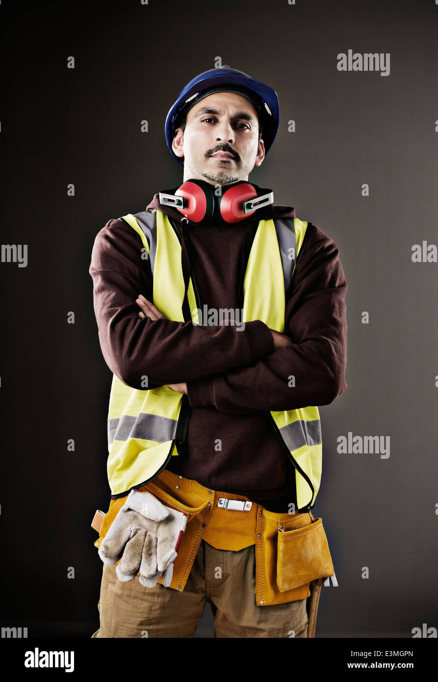 Portrait of serious worker in reflective clothing - Stock Image