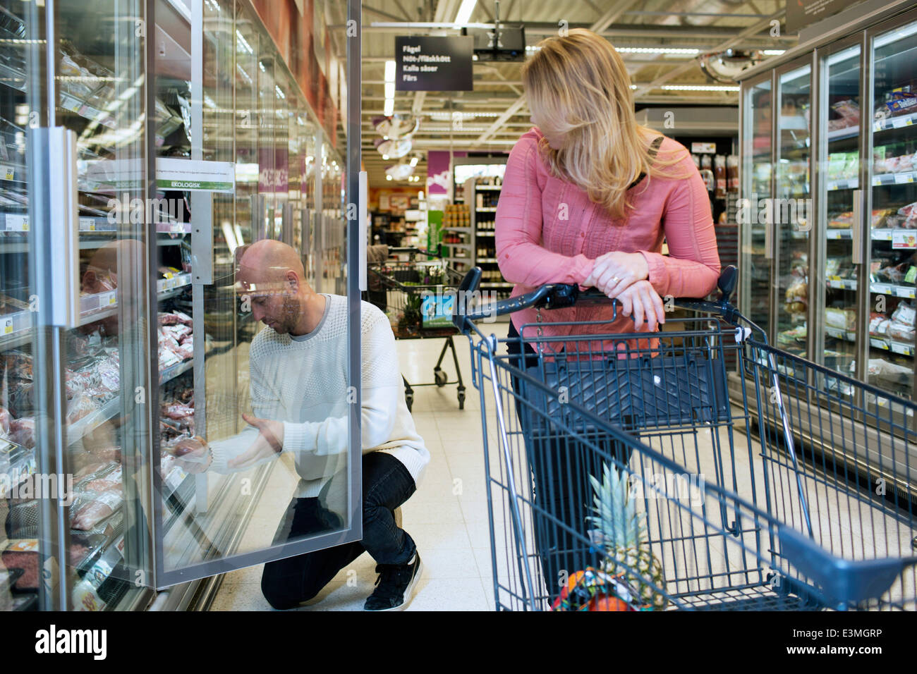 Mid adult couple buying groceries in supermarket - Stock Image