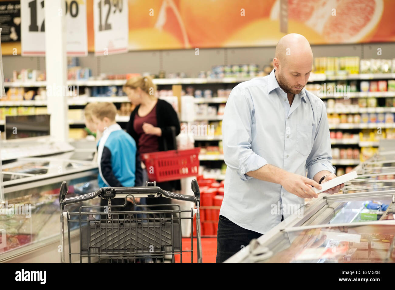 Mid adult man examining product with family in background in grocery store - Stock Image