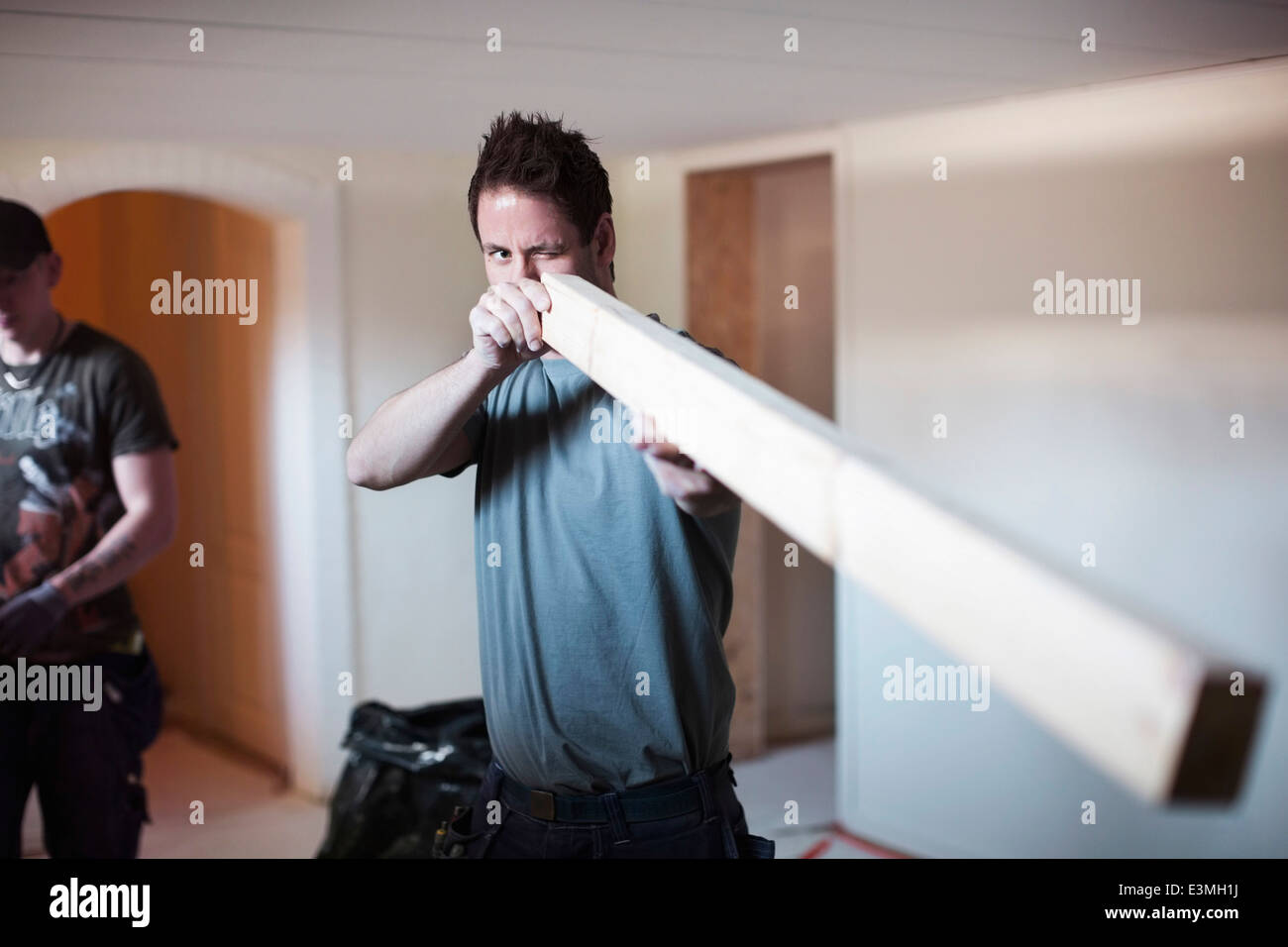 Male carpenter examining wooden plank at site - Stock Image