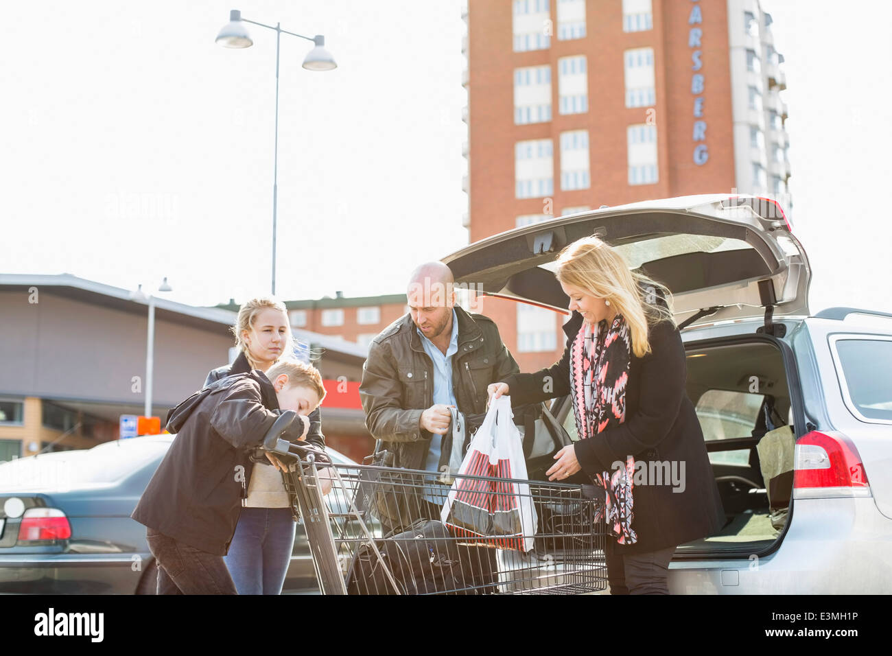 Family loading groceries in car trunk at parking lot - Stock Image