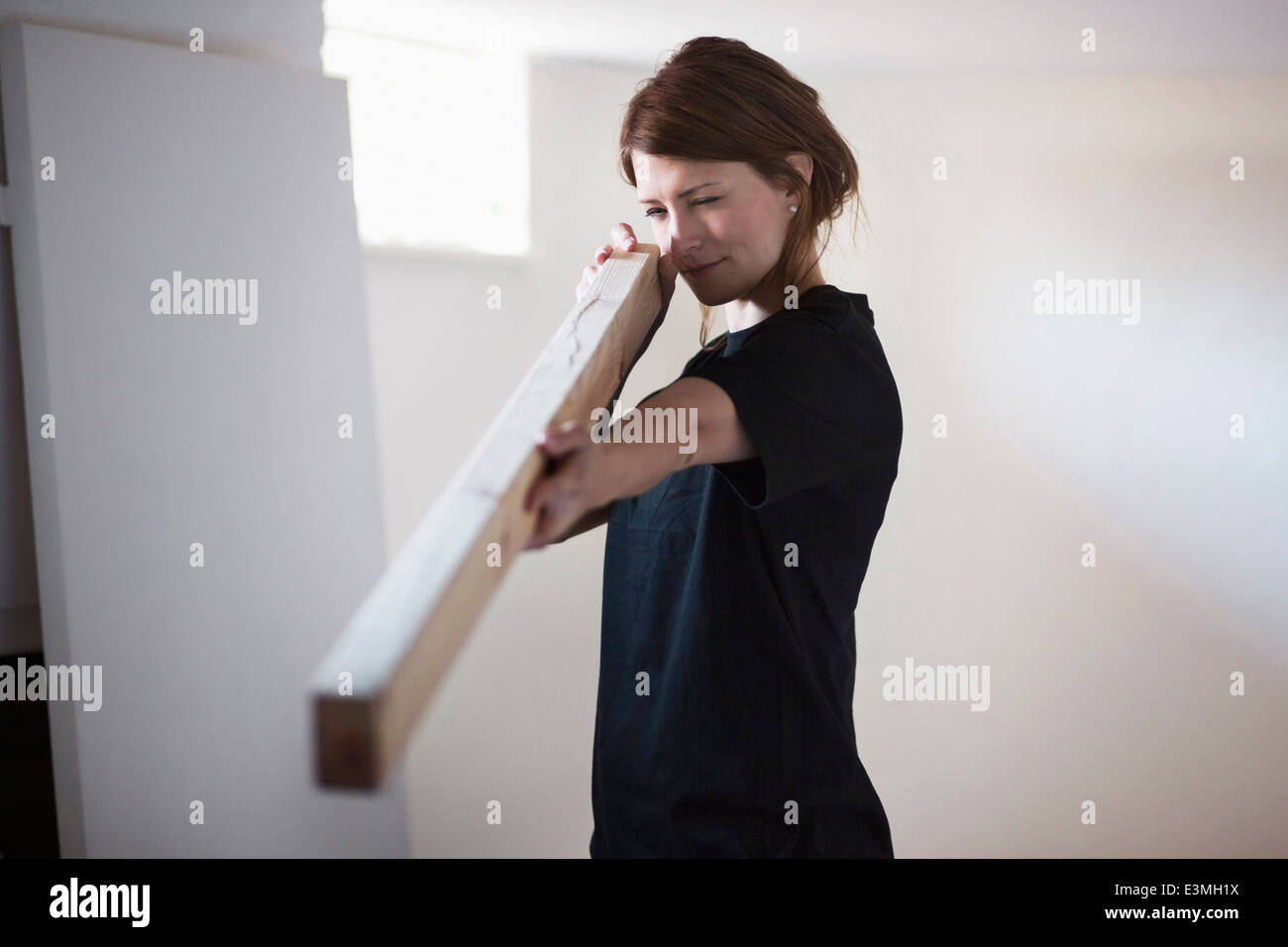 Female carpenter examining wooden plank at site - Stock Image