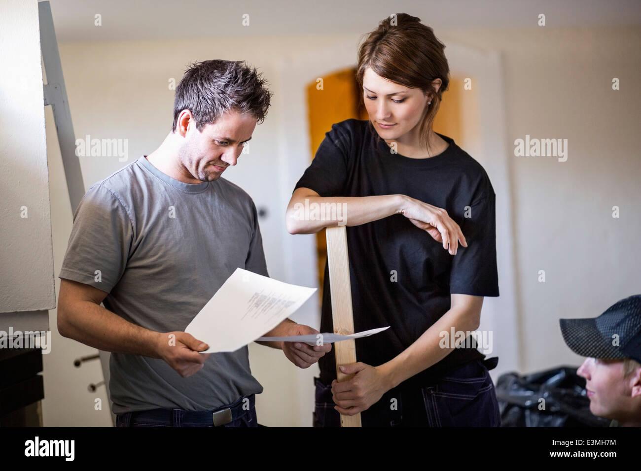 Carpenters examining documents at site - Stock Image