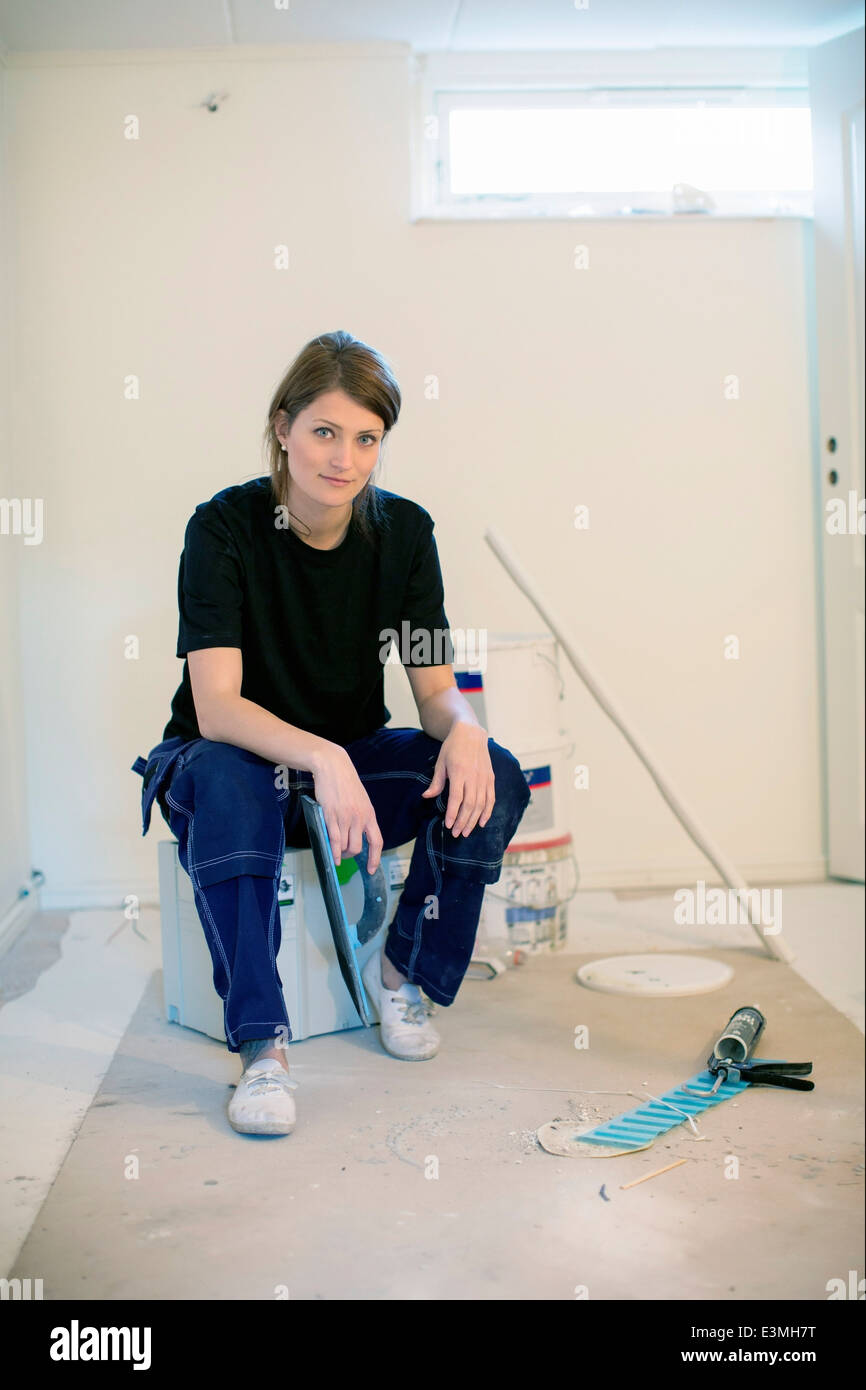 Full length portrait of confident female carpenter at site - Stock Image