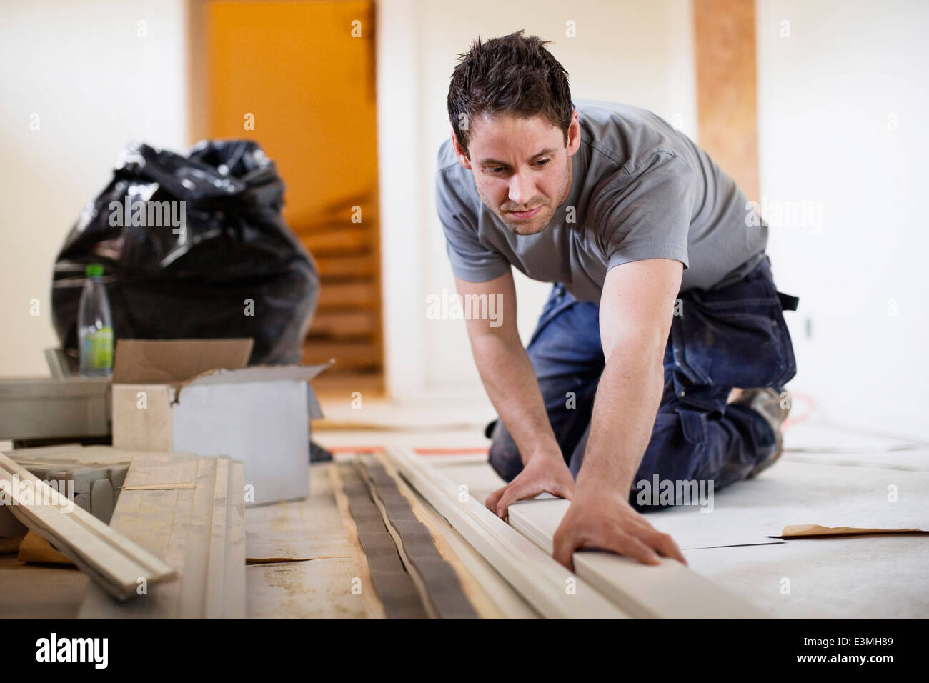 Male carpenter examining wooden plank at site Stock Photo