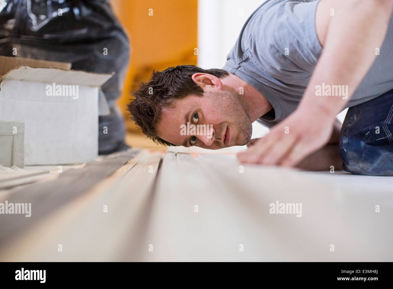 Male carpenter checking wooden plank at site Stock Photo
