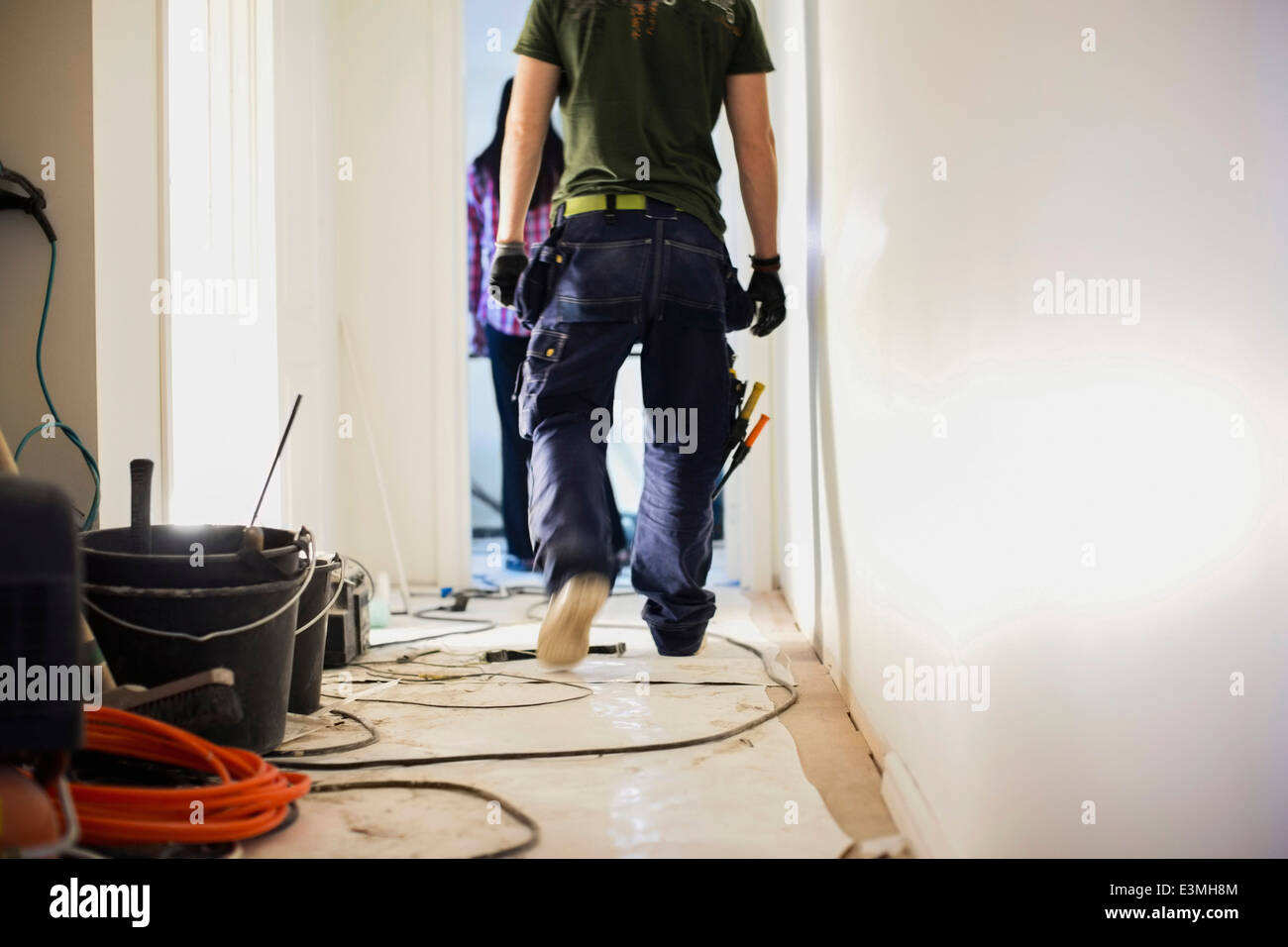 Low section of carpenter walking in corridor at construction site - Stock Image