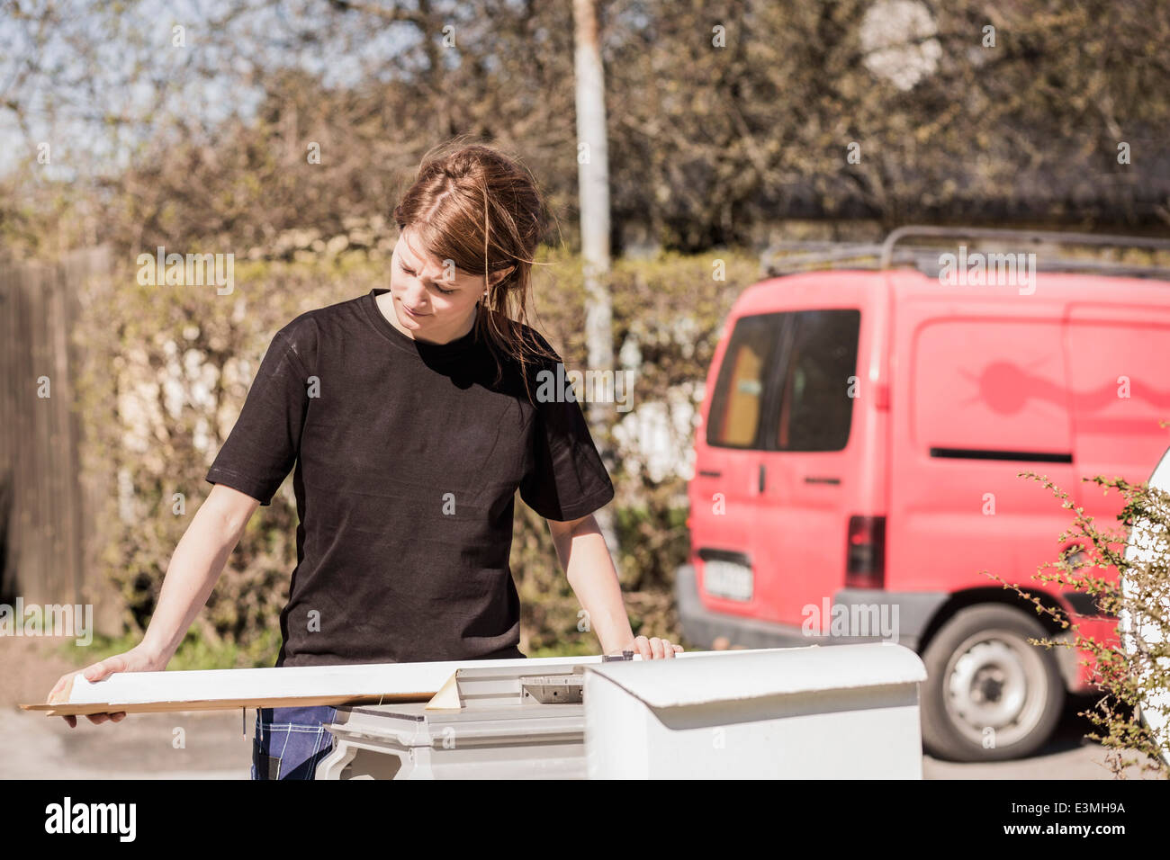 Female carpenter examining wooden plank outdoors - Stock Image