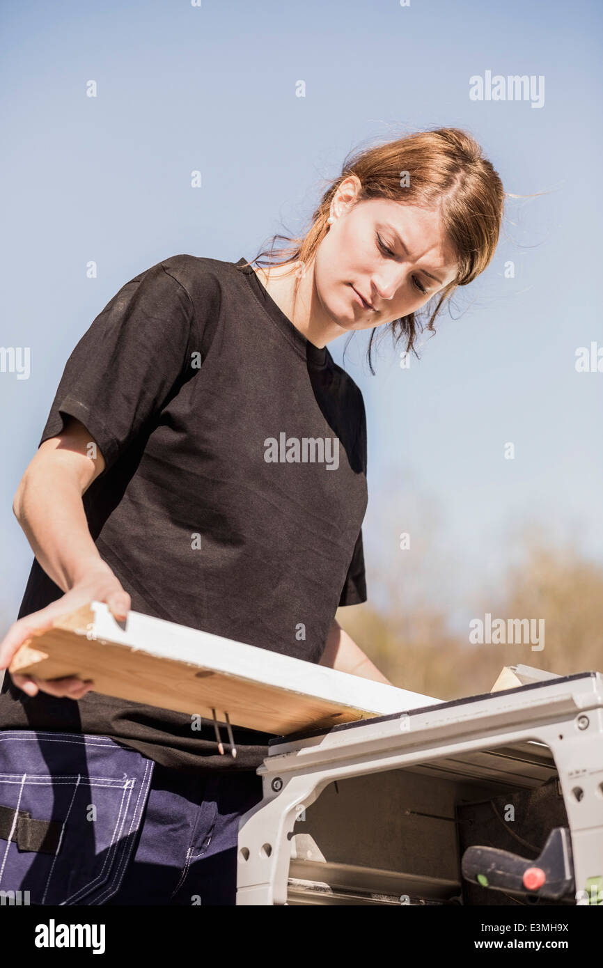 Low angle view of female carpenter working outdoors Stock Photo