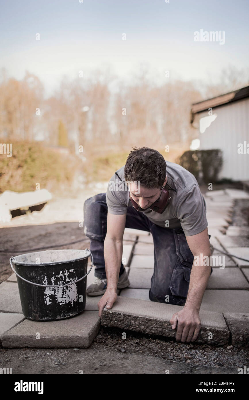 Male carpenter positioning stone tile in yard - Stock Image