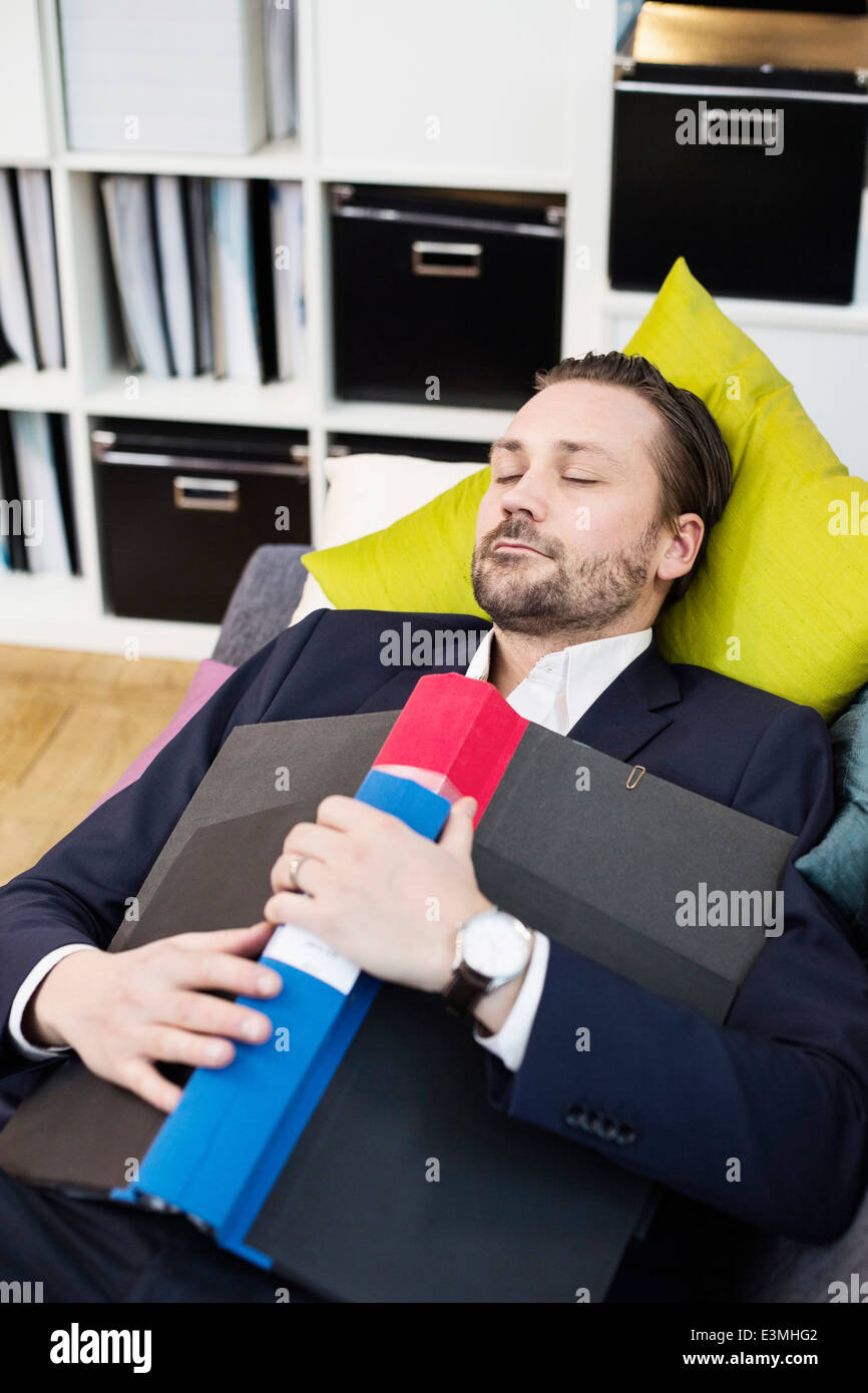 Mid adult businessman with folder sleeping on sofa in office - Stock Image