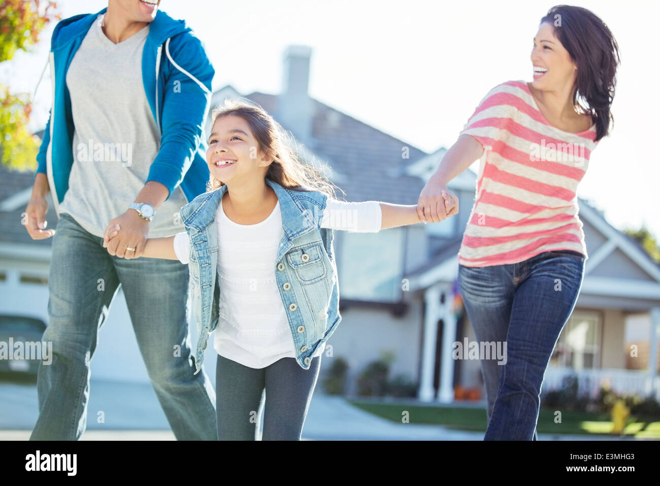 Happy family holding hands and running - Stock Image