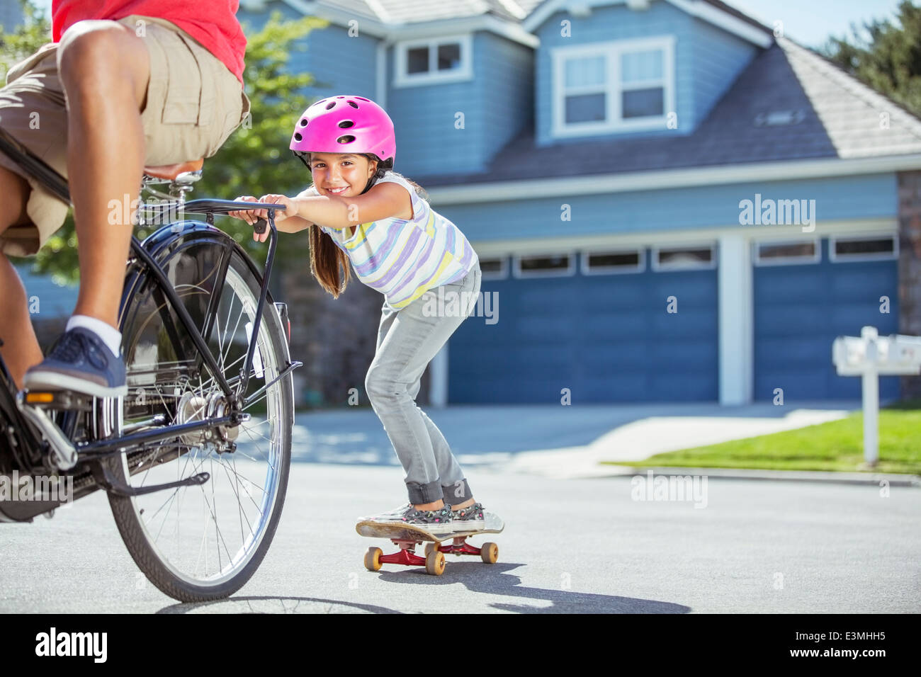 Father on bicycle pulling daughter on skateboard - Stock Image