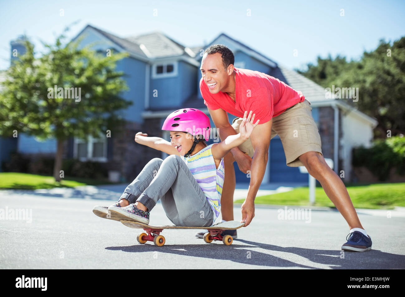 Father pushing daughter on skateboard - Stock Image