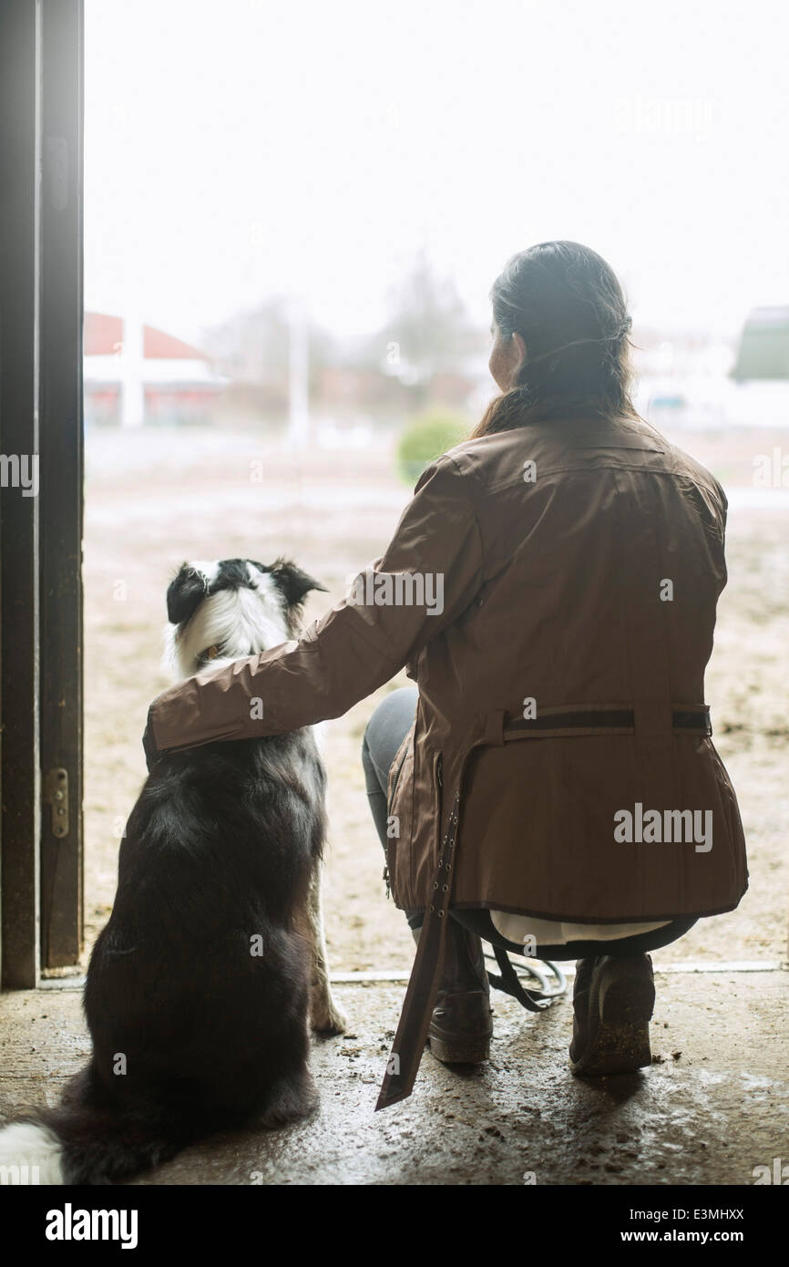 Full length rear view of young woman arm around dog in doorway of horse stable - Stock Image