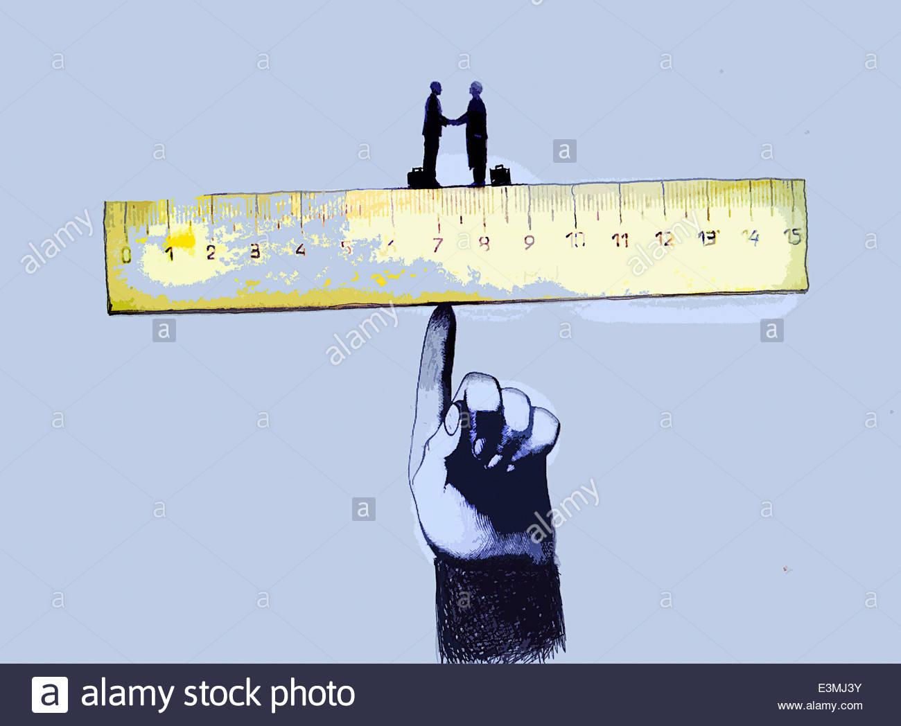 Businessmen shaking hands on ruler balanced on large finger - Stock Image