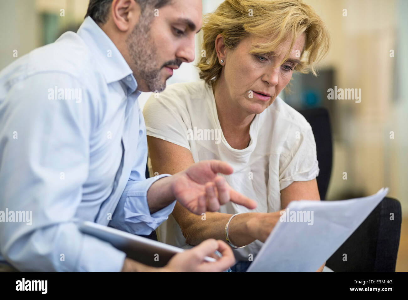 Businesspeople discussing over document in meeting at office - Stock Image