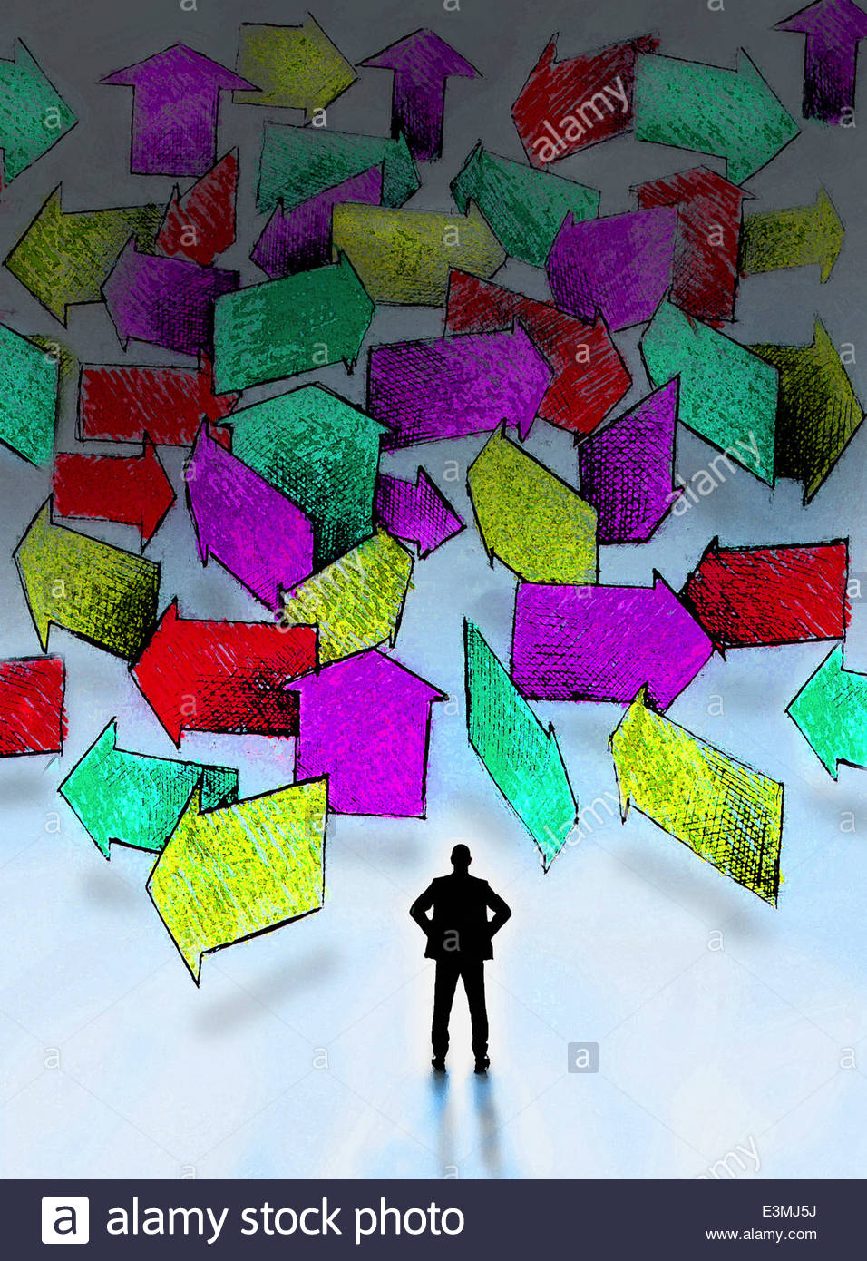 Businessman standing in front of lots of multicolored arrows pointing in different directions - Stock Image
