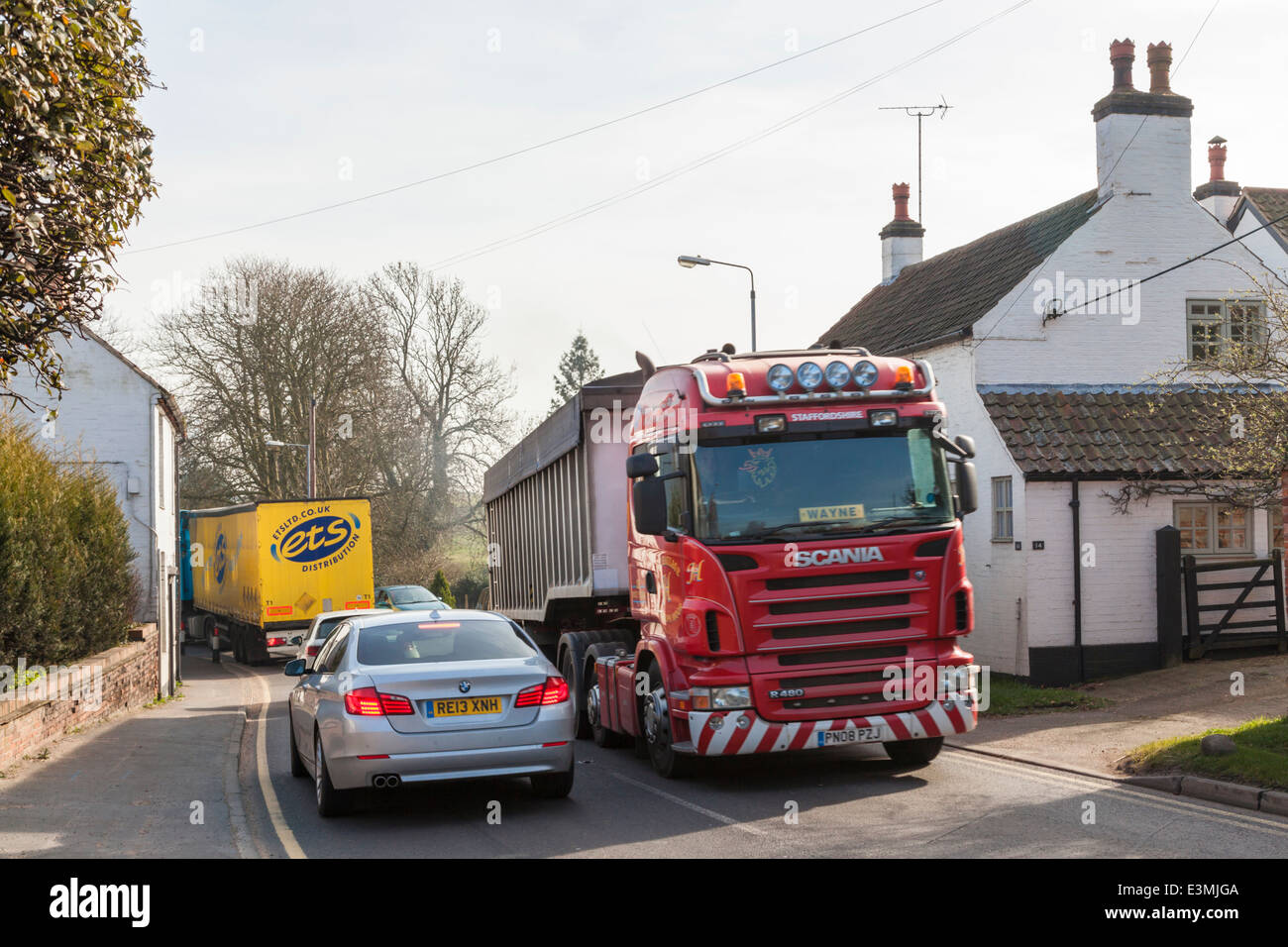 Traffic jam with lorries and cars passing close to houses in the rural village of Rempstone, Nottinghamshire, England, - Stock Image