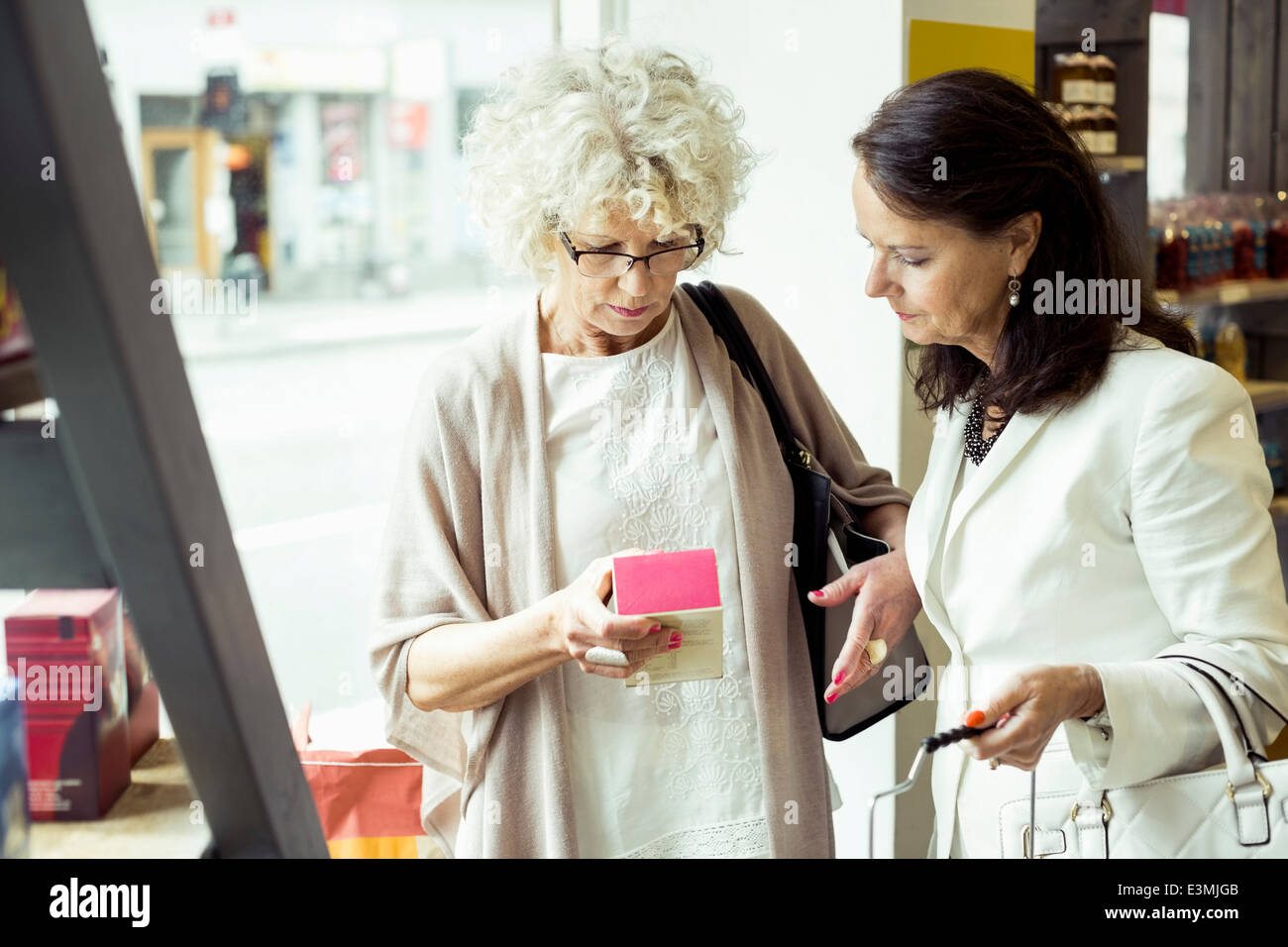 Senior women reading label on product in store - Stock Image