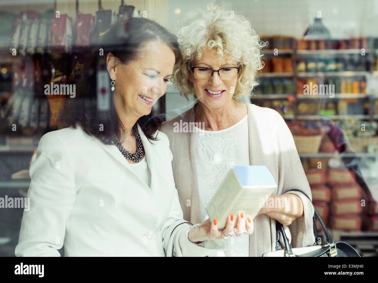 Senior women checking instructions on product in store - Stock Image