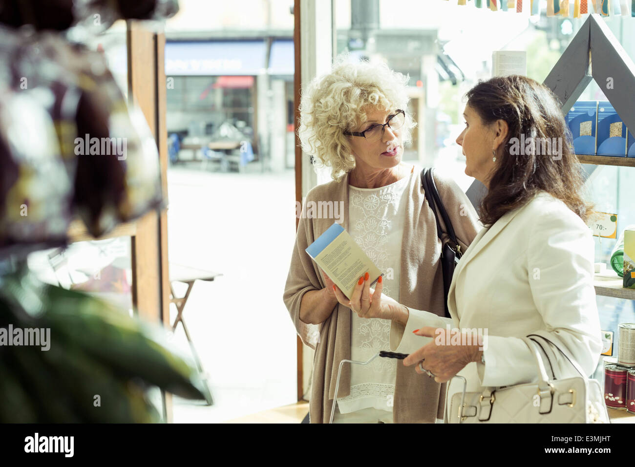 Senior women discussing over product in store - Stock Image